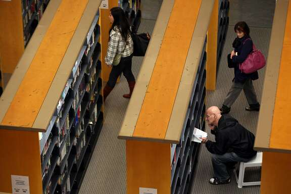 SAN FRANCISCO, CA - JANUARY 11:  A library patron looks at a book at the main branch of the San Francisco Public Library on January 11, 2011 in San Francisco, California. California governor Jerry Brown proposed his budget on Monday that includes deep cut