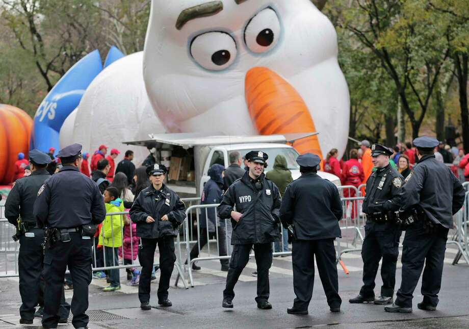 """Police officers stand near the site where a large balloon of the character Olaf from """"Frozen"""" is being inflated for the Thanksgiving Day parade in New York, Wednesday, Nov. 22, 2017. Sand-filled sanitation trucks and police sharpshooters will mix with glittering floats and giant balloons at a Macy's Thanksgiving Day Parade that comes in a year of terrible mass shootings and a deadly truck attack in lower Manhattan. (AP Photo/Seth Wenig) ORG XMIT: NYSW102 Photo: Seth Wenig / Copyright 2017 The Associated Press. All rights reserved."""