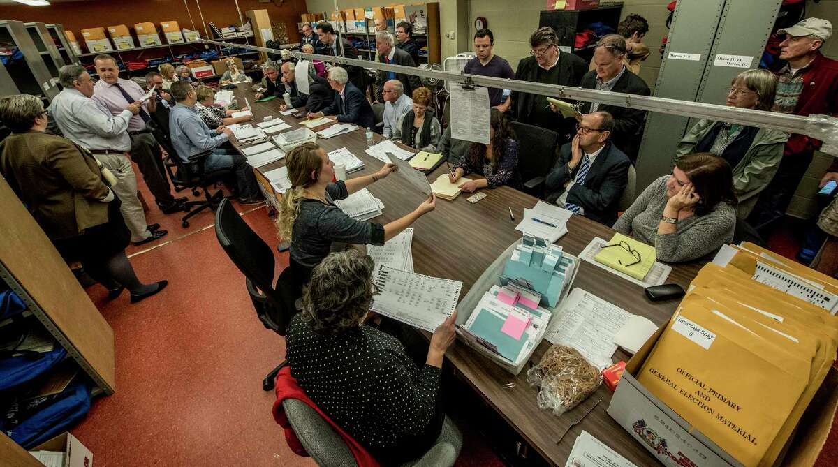 Representatives from the Democrats and the Republicans huddle up over the recount of absentee ballots in the City of Saratoga election as they look closely at the City Charter vote and the race for the Public Safety Commissioner Tuesday Nov. 14, 2017 at the Saratoga County Board of Elections offices in Ballston Spa, N.Y. (Skip Dickstein/ Times Union)