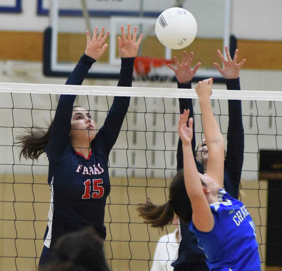 GFA volleyball player Kristiana Modzelewski, left, blocks a shot during the Dragons' New England Class C tournament quarterfinal at Coyle Gym in Westport last week. Photo: Contributed Photo