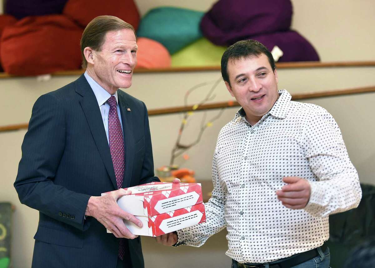 U.S. Senator Richard Blumenthal, left, delivers pies from Oronoque Farms for Thanksgiving to Marco Reyes at First and Summerfield United Methodist Church in New Haven Wednesday, where he had been taking sanctuary.