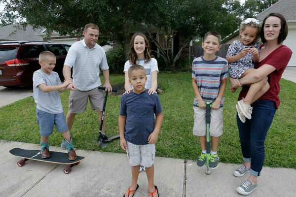 Cliff Conner, second from left, and Stacey Conner with their children, Shepard, 8, left, Grace, 11, Cliff, 6, Isaac, 9, and Kelley, 4, right, as they play outside the home they rent in Spring.
