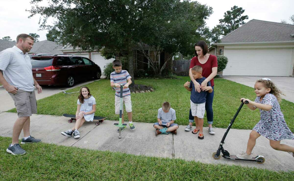 Cliff Conner, left, and Stacey Conner with their children, Grace, 11, sitting left, Isaac, 9, Shepard, 8, Cliff, 6, and Kelley, 4, right, as they play outside the home they rent in Spring Wednesday, Nov. 15, 2017. ( Melissa Phillip / Houston Chronicle )