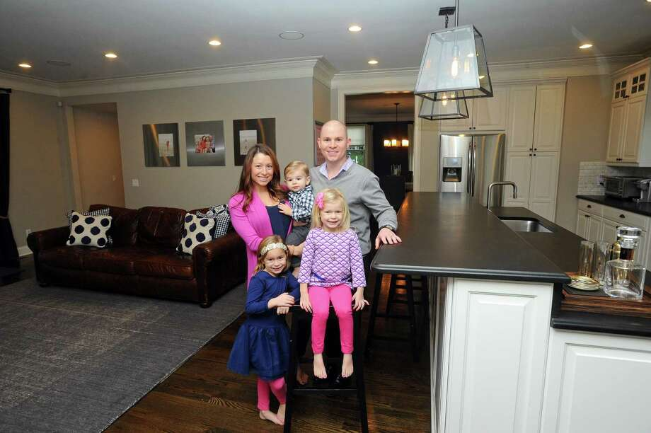 William and Jenny Jarvis pose for a photo with their children Ellie, Holland and William inside the large kitchen and living room inside their five-bedroom Shippan home on Ocean Drive West in Stamford, Conn. on Wednesday, Nov. 22, 2017. The Jarvis family is trading their 4,000-square-foot Shippan colonial, which was built in 2010, for a house in Greenwich closer to where their children attend school. Photo: Michael Cummo / Hearst Connecticut Media / Stamford Advocate