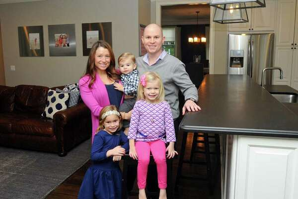 William and Jenny Jarvis pose for a photo with their children Ellie, Holland and William inside the large kitchen and living room inside their five-bedroom Shippan home on Ocean Drive West in Stamford, Conn. on Wednesday, Nov. 22, 2017. The Jarvis family is trading their 4,000-square-foot Shippan colonial, which was built in 2010, for a house in Greenwich closer to where their children attend school.