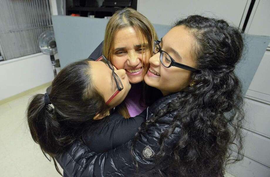 Miriam Martinez Lemus, center, is hugged by her daughters, Allison Benavides,10, left, and Brianna Benavides,12. Photo: Matthew Brown / Hearst Connecticut Media / Stamford Advocate