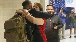 Barbara Sosa hugs her son Michael Sosa (facing away with backpack) Wednesday November 22, 2017 at the San Antonio International Airport as he returns home after two years of missionary work in the midwest United States. Wednesday was a busy day at the airport with travelers heading in and out of San Antonio for the Thanksgiving holiday.