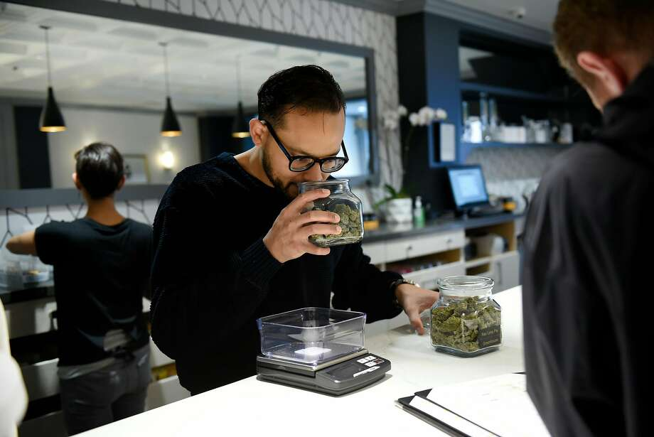Patient consultant team leader Lee Coleman smells a jar of buds while helping a customer at the Apothecarium medical cannabis dispensary in San Francisco. Photo: Michael Short, Special To The Chronicle