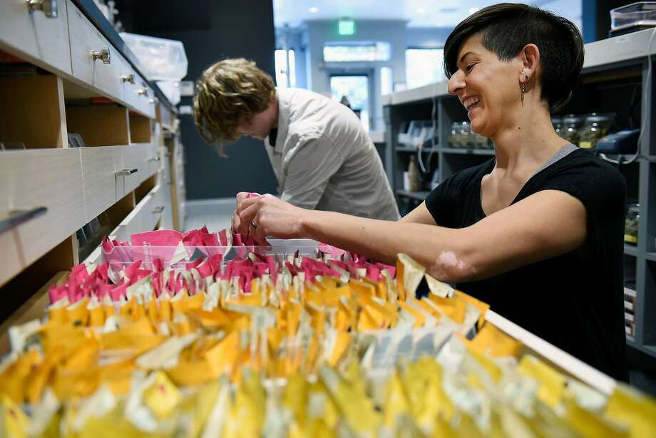 Patient consultant Melissa Zoppa jokes with fellow consultant Nick Finch as they restock drawers with edible cannabis products at medical cannabis dispensary the Apothecarium in San Francisco. Photo: Michael Short, Special To The Chronicle