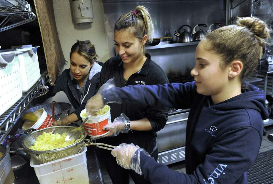 From left, Becca Martin, Libby Martin and Madison NeJaime, prepare ambrosia fruit salad for Thursday's Thanksgiving meal, Wed. Nov. 22, 2017. This is the 14th year the Easley family has coordinated a dinner in memory of Dustin Easley, who died in a motor vehicle accident Thanksgiving morning 2003. Photo: Carol Kaliff / Hearst Connecticut Media / The News-Times