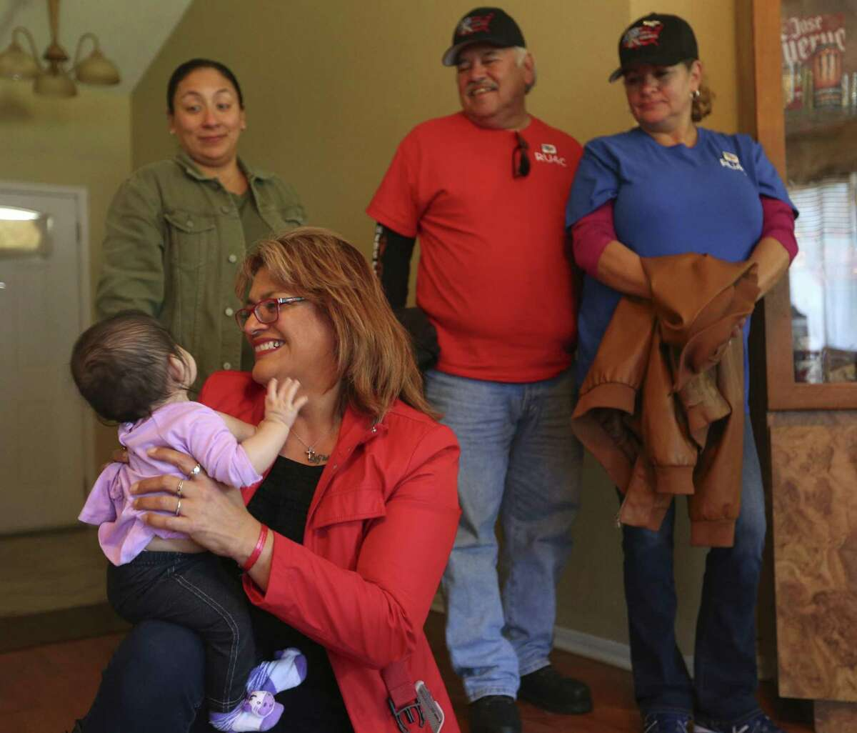 Pamela Allen plays Wednesday Nov. 22, 2017 with a child in the care of Frances Martinez as Allen and other members from Eagles Flight Advocacy & Outreach and volunteers from the Bank of San Antonio deliver food for a Thanksgiving meal to Martinez's home.