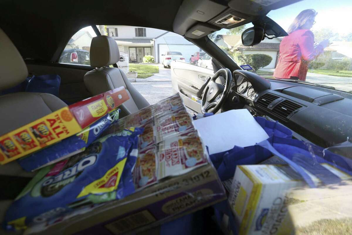 Pamela Allen's car is full Wednesday, Nov. 22, 2017 with food from Eagles Flight Advocacy & Outreach and volunteers from the Bank of San Antonio as they deliver meals to families for Thanksgiving dinner.