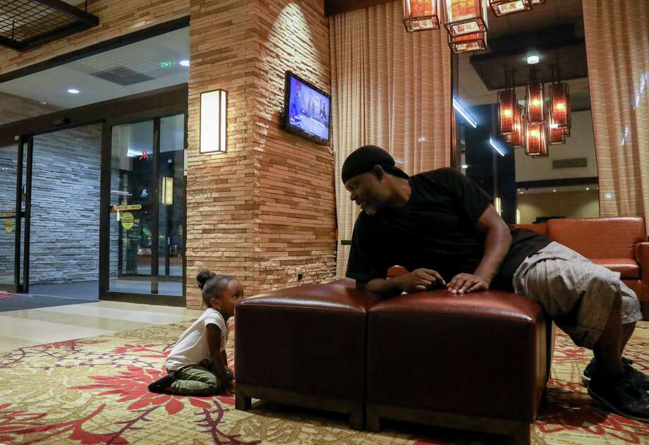 Mikey Robinson, left, plays with his girlfriend's daughter, Nori Nolan, 3, in the lobby of a hotel in the Greenspoint area, Wednesday, Nov. 15, 2017, in Houston. Photo: Jon Shapley, Houston Chronicle / © 2017 Houston Chronicle