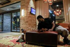 Mikey Robinson, left, plays with his girlfriend's daughter, Nori Nolan, 3, in the lobby of a hotel in the Greenspoint area, Wednesday, Nov. 15, 2017, in Houston.
