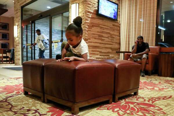 Nori Nolan, 3, plays in the lobby of a hotel in the Greenspoint area, while her mother's boyfriend, Mikey Robinson, right, talks on the phone, Wednesday, Nov. 15, 2017, in Houston.