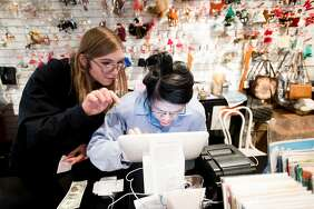 Megan Dabrowski (left), employment services manager for the Arc San Francisco, helps client Connie Chu work a cash register at Helpers Bazaar in Ghirardelli Square.