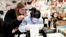 Megan Dabrowski, left, employment services manager for The Arc San Francisco, helps client Connie Chu work a cash register at Helpers Bazaar on Wednesday, Nov. 22, 2017, in San Francisco.