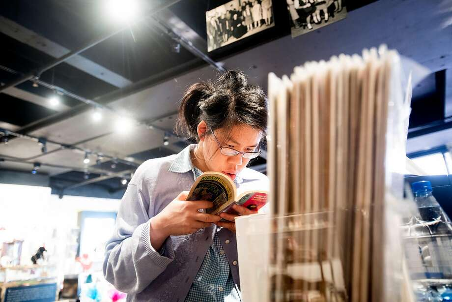 Connie Chu, a client at the Arc San Francisco, reads a comic book during down time at Helpers Bazaar. Photo: Noah Berger, Special To The Chronicle