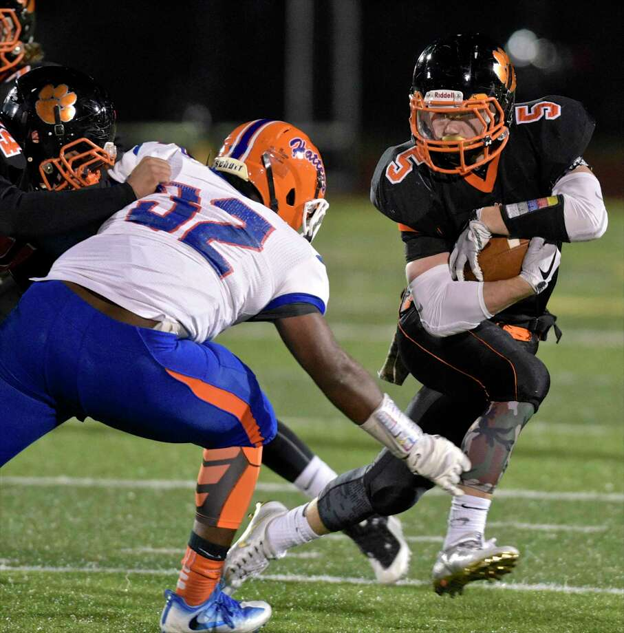 Ridgefield's Benjamin Seward (5) cuts across the path of Danbury's Solomon James (32) in the football game between Danbury and Ridgefield high schools on Wednesday night, November 22, 2017, at Ridgefield High School, in Ridgefield, Conn. Photo: H John Voorhees III, Hearst Connecticut Media / The News-Times