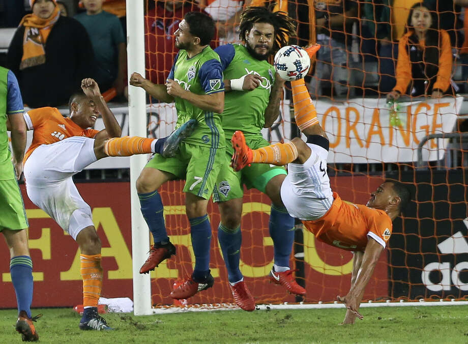 After falling behind 2-0, the Dynamo came up empty Wednesday night, with Juan Cabezas, right, trying a bicycle kick  and Mauro Manotas missing the ball but hitting a Sounder on this play in second half. Photo: Yi-Chin Lee, Houston Chronicle / © 2017  Houston Chronicle