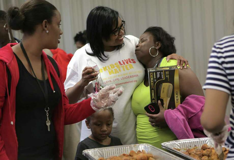 Kids Lives Matter executive director Catherine Smith, hugs an attendee of their annual Thanksgiving community outreach event for more than 1,500 less fortunate children and families at Cuney Homes Apartments on Wednesday, Nov. 22, 2017, in Houston. ( Elizabeth Conley / Houston Chronicle ) Photo: Elizabeth Conley, Chronicle / © 2017 Houston Chronicle