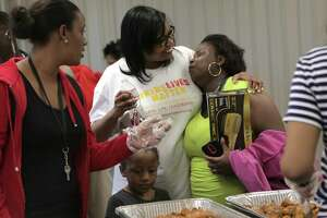 Kids Lives Matter executive director Catherine Smith, hugs an attendee of their annual Thanksgiving community outreach event for more than 1,500 less fortunate children and families at Cuney Homes Apartments on Wednesday, Nov. 22, 2017, in Houston. ( Elizabeth Conley / Houston Chronicle )