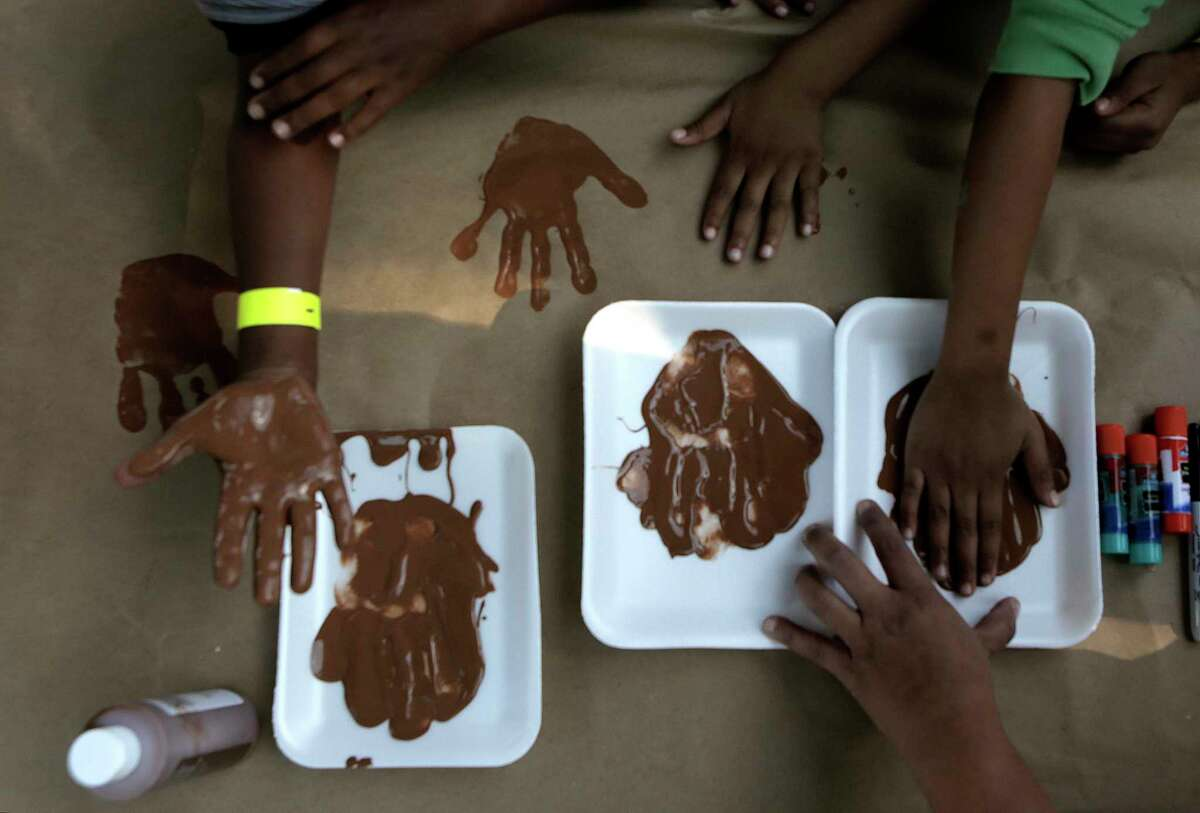 Children make turkeys out of their hand prints during a Kids Lives Matter's Thanksgiving community outreach event for more than 1,500 less fortunate children and families at Cuney Homes Apartments on Wednesday, Nov. 22, 2017, in Houston. ( Elizabeth Conley / Houston Chronicle )