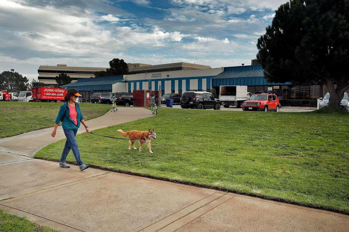 """A woman walks her dog near the warehouse office spaces at Oyster Point Marina where a proposed development of 1100 residential units is being encouraged by the city of South San Francisco, Calif., Wednesday, November 22, 2017. The area east of Hwy 101 has long been the heart of South San Francisco's business base - the engine behind the town's historic claim to be """"The Industrial City."""""""