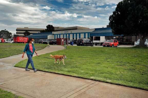 "A woman walks her dog near the warehouse office spaces at Oyster Point Marina where a proposed development of 1100 residential units is being encouraged by the city of South San Francisco, Calif., Wednesday, November 22, 2017. The area east of Hwy 101 has long been the heart of South San Francisco's business  base - the engine behind the town's historic claim to be ""The Industrial City."""
