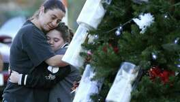 Melissa Salinas (left) hugs Paige Burleson as visitors gather around a Christmas tree Wednesday at the Sutherland Springs Community Building. The tree features 26 angels, one for each the lives lost in the Nov. 5 massacre at the First Baptist Church, and 20 other ornaments, tied with ribbons, that represent those who were wounded.