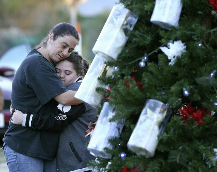 Melissa Salinas (left) hugs Paige Burleson as visitors gather around a Christmas tree at the Sutherland Springs Community Building. Twenty-six angels and 20 other ornaments adorn the tree, representing the dead and wounded from the mass shooting at the Baptist church. A pastor from another reminds the community that the world is still thinking about them.