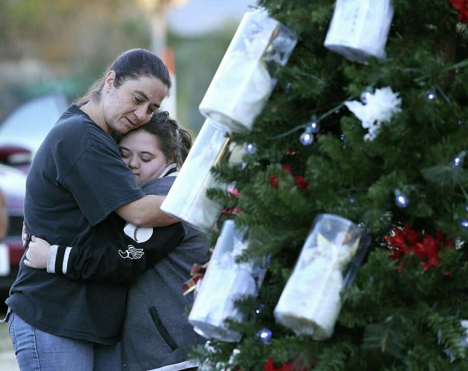 Melissa Salinas (left) hugs Paige Burleson as visitors gather around a Christmas tree at the Sutherland Springs Community Building. Twenty-six angels and 20 other ornaments adorn the tree, representing the dead and wounded from the mass shooting at the Baptist church. A pastor from another reminds the community that the world is still thinking about them. Photo: Tom Reel /San Antonio Express-News / 2017 SAN ANTONIO EXPRESS-NEWS