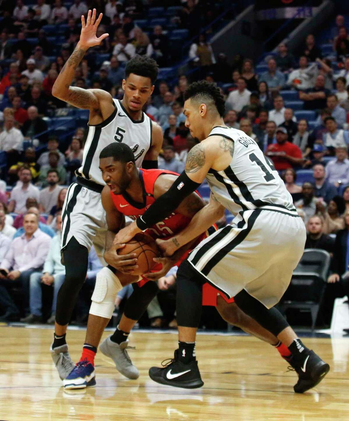 San Antonio Spurs guard Danny Green (14) steals the ball from New Orleans Pelicans forward E'Twaun Moore (55) as guard Dejounte Murray (5) defends in the first half of an NBA basketball game in New Orleans, Wednesday, April 11, 2018. (AP Photo/Scott Threlkeld)