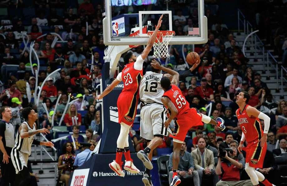 San Antonio Spurs forward LaMarcus Aldridge (12) takes a shot between New Orleans Pelicans forward Anthony Davis (23) and forward E'Twaun Moore (55) in the first half of an NBA basketball game in New Orleans, Wednesday, April 11, 2018. (AP Photo/Scott Threlkeld) Photo: Scott Threlkeld, Associated Press / FR171144 AP