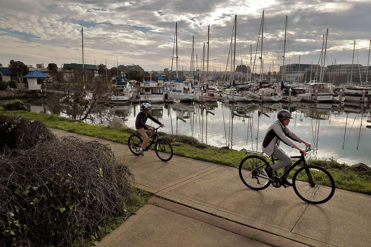 """Cyclists ride by the Oyster Point Marina where a proposed development of 1100 residential units is being encouraged by the city of South San Francisco, Calif., Wednesday, November 22, 2017. The area east of Hwy 101 has long been the heart of South San Francisco's business base - the engine behind the town's historic claim to be """"The Industrial City."""""""