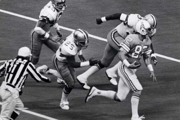 The Oilers' Mike Renfro heads for a 47-yard touchdown, one of two TD passes thrown by quarterback Dan Pastorini in a Nov. 22, 1979, game against the Cowboys at Texas Stadium. The other, a 32-yarder to Kenny Burrough, won the game.