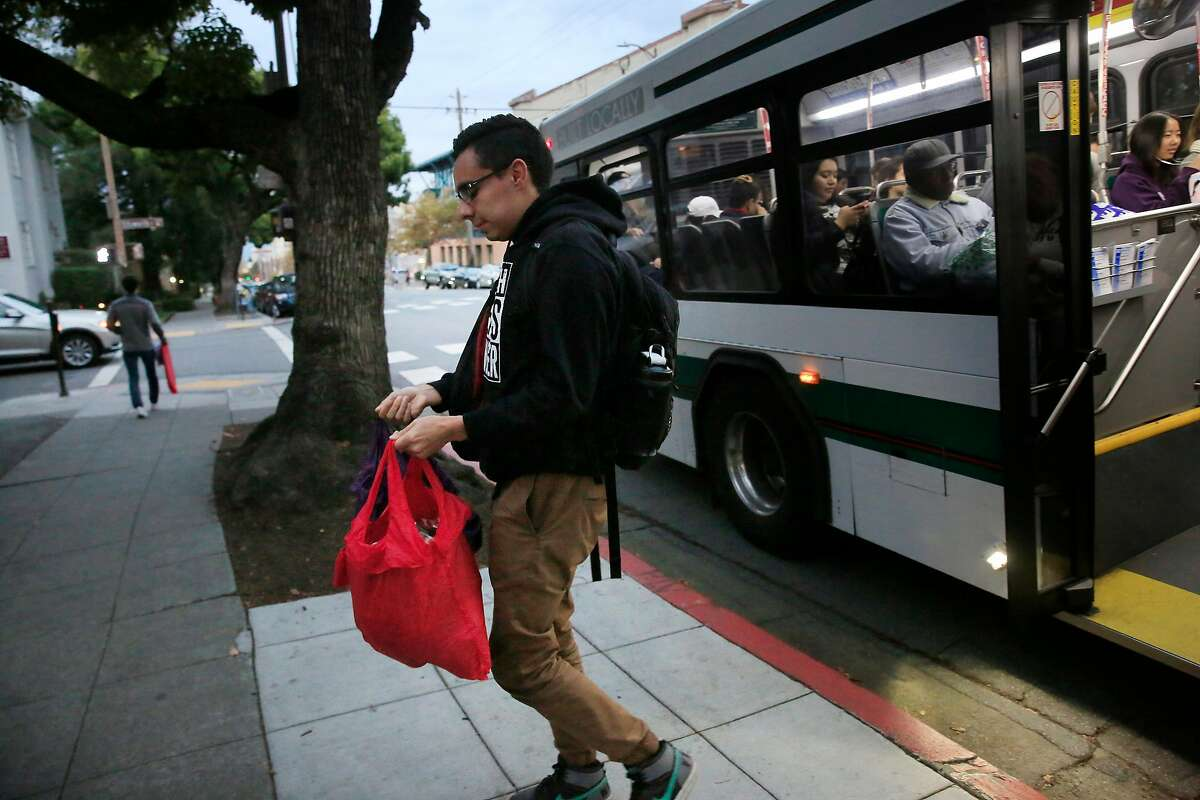 Esteban Vasquez, a UC Berkeley senior, gets off a bus with bags of groceries he bought with CalFresh food stamps.