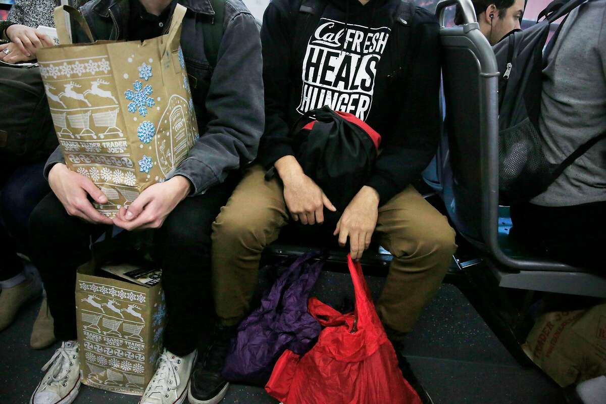 Esteban Vasquez (right), UC Berkeley senior, sits with his bags of groceries from a market after shopping on Wednesday, November 15, 2017 in Berkley, Calif. Vasquez is able to use CalFresh to buy some of his groceries.