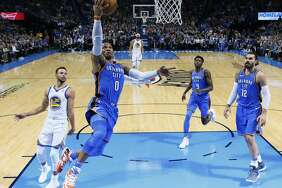 Oklahoma City Thunder guard Russell Westbrook (0) goes up for a shot in front of Golden State Warriors guard Stephen Curry (30) and Thunders' Jerami Grant (9) and Steven Adams (12) during the first quarter of an NBA basketball game in Oklahoma City, Wednesday, Nov. 22, 2017. (AP Photo/Sue Ogrocki)