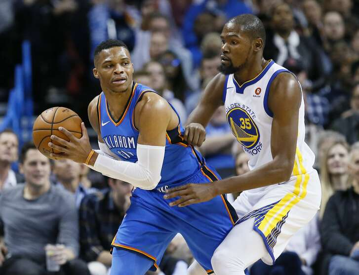 Oklahoma City Thunder guard Russell Westbrook, left, keeps the ball from Golden State Warriors forward Kevin Durant during the first quarter of an NBA basketball game in Oklahoma City, Wednesday, Nov. 22, 2017. (AP Photo/Sue Ogrocki)