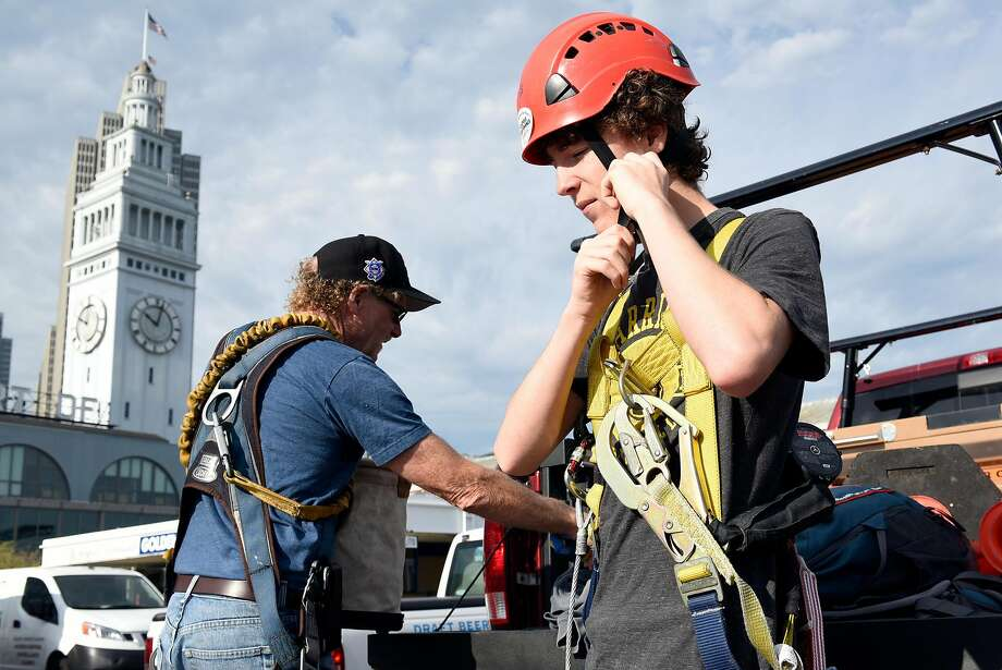 """Jim and Kells Phelan put on gear as they prepare to climb the flagpole. """"You have to respect the job,"""" says Kells, the fourth generation of climbing Phelans. Photo: Michael Short, Special To The Chronicle"""