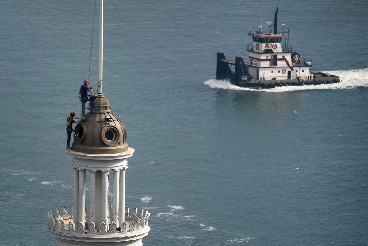 A tug boat passes by as Jim Phelan, top, and his son and apprentice steeplejack Kells Phelan, inspect the flagpole atop the Ferry Building clock tower, in San Francisco, CA, on Wednesday November 22, 2017.