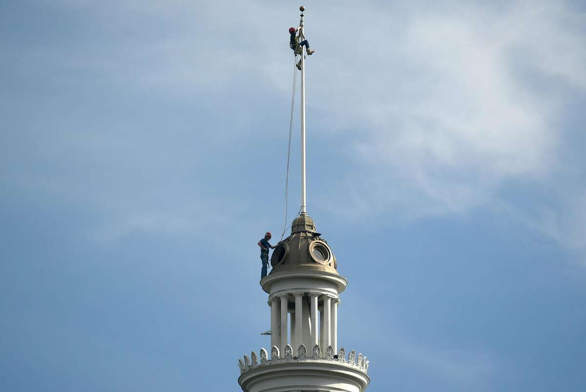 Jim Phelan, bottom, and his son and apprentice steeplejack Kells Phelan, inspect the flagpole atop the Ferry Building clock tower, in San Francisco, CA, on Wednesday November 22, 2017.