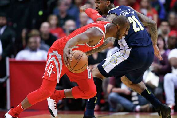 Houston Rockets guard Chris Paul, left, dribbles past Denver Nuggets forward Wilson Chandler during the first half of an NBA basketball game, Wednesday, Nov. 22, 2017, in Houston. (AP Photo/Eric Christian Smith)