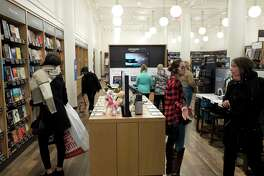 Customers browse at an Amazon Books store, Monday, Nov. 20, 2017, in New York. Amazon goes into the holiday season with a newly magnified brick-and-mortar presence, giving it more opportunities to sell its Kindle e-readers, Fire tablets and other gadgets. The online retailer now has more than a dozen Amazon Books stores, which also sell toys, electronics and small gifts. (AP Photo/Mark Lennihan)