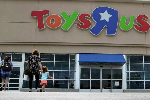 FILE - In this Tuesday, Sept. 19, 2017, file photo, shoppers walk into a Toys R Us store, in San Antonio. Some of the hottest toys this year are LOL Surprise and Pikmi Pops. These and similar toys hide small stuffed animals or dolls inside plastic balls that are wrapped in several layers of packaging. Kids peel each layer, revealing tiny bags filled with trinkets, stickers, messages or other doll accessories as they go. (AP Photo/Eric Gay, File)