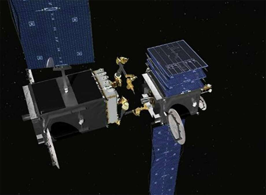 This rendering shows robotic arms that are being built for the Defense Advanced Research Projects Agency. The robotic servicer, on the left, is preparing to use a tool to open a stuck solar array on a disabled satellite. Photo: SSL, HO / Los Angeles Times