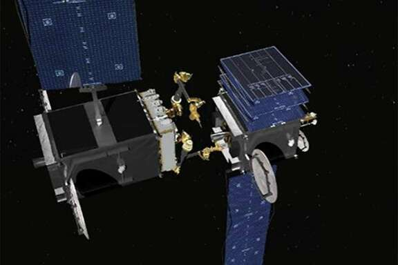This rendering shows robotic arms that are being built for the Defense Advanced Research Projects Agency. The robotic servicer, on the left, is preparing to use a tool to open a stuck solar array on a disabled satellite.