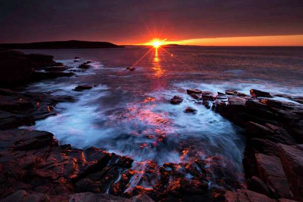 FILE- In this May 2, 2013 file photo, the sun's rays strike the rocky coast of Acadia National Park on Mt. Desert Island in Maine. A group of state attorneys general on Wednesday urged the National Park Service to scrap its proposal to more than double the entrance fee at 17 popular national parks. (AP Photo/Robert F. Bukaty, File)