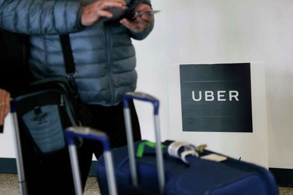 FILE - In this Wednesday, March 15, 2017, file photo, a traveler tries to book a ride with Uber at LaGuardia Airport in New York. Through a string of almost weekly scandals, Uber has managed to continue growing and hold onto the title of the world's largest ride-hailing service. In the latest misbehavior, hackers were able to steal data for 57 million riders and drivers, and Uber concealed it for a year. Riders and business experts say that hits people directly, and they won't be happy about it. (AP Photo/Seth Wenig, File)